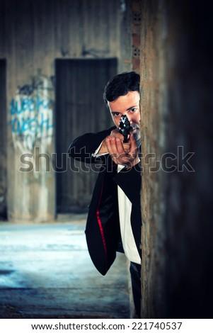 Hitman in tuxedo holding a gun - stock photo