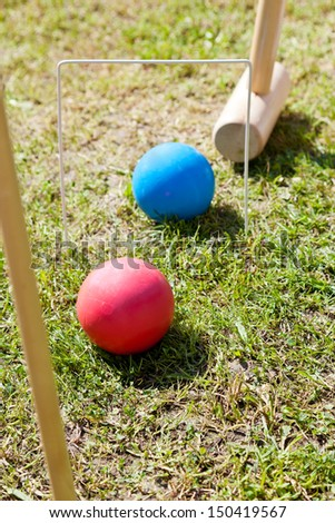 hitting blue ball through hoop in game of croquet on green lawn - stock photo