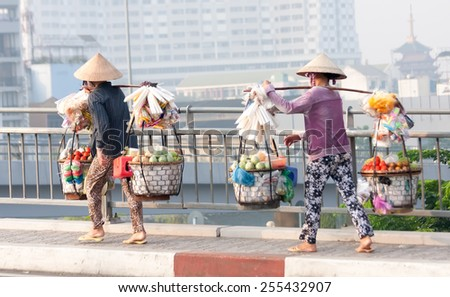 Ho Chi Minh City-Nov 1st: Street vendors crossing the bridge over the river on the way back from the market. Vendors can be found all over the city. - stock photo