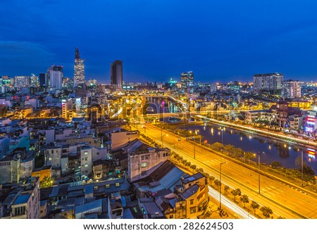 HO CHI MINH CITY / VIETNAM - DEC 10 2014: Ho Chi Minh Riverside cityscape night view with Ben Nghe or Tau Hu canal and calmet Bridge - stock photo