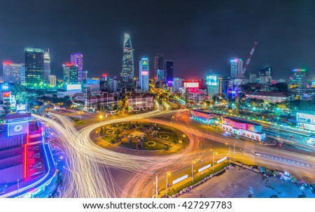Ho Chi Minh City, Vietnam - July 23rd, 2015: Impressive beauty, colorful traffic when city lights up, trail vehicle in crowded Quach Thi Trang roundabout, Ho Chi Minh city, Vietnam - stock photo