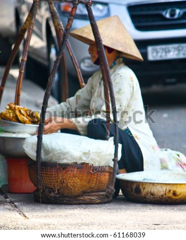 HO CHI MINH CITY, VIETNAM - JUNE 11 : A Vietnamese lady squats by the road side and selling food to the public. June 11, 2010 Ho Chi Minh City, Vietnam - stock photo