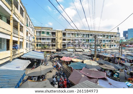 HO CHI MINH CITY, VIETNAM - MARCH 15, 2015: Typical of old apartment buildings with impression scene of cement wall, block downgrade and the street market standing below colorful umbrellas - stock photo