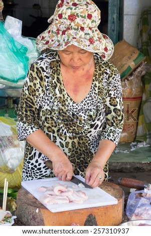 Ho Chi Minh City, Vietnam-Nov 2nd 2013: Woman fishmonger cutting up fish on Cholon market. Cholon is the Chinatown area of the city. - stock photo
