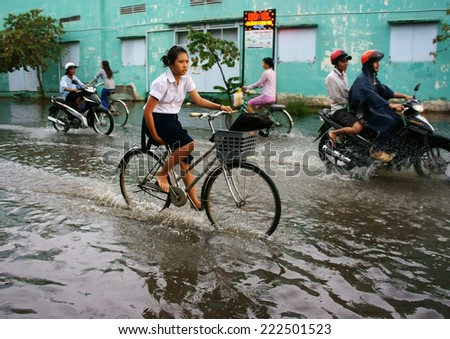 HO CHI MINH CITY, VIETNAM- OCT 9: Hard to circulate situation at Ho Chi Minh city when flood tide, flooded water on street, vehicle traffic in water, danger, unsafe scene, Vietnam, Oct 9, 2014 - stock photo
