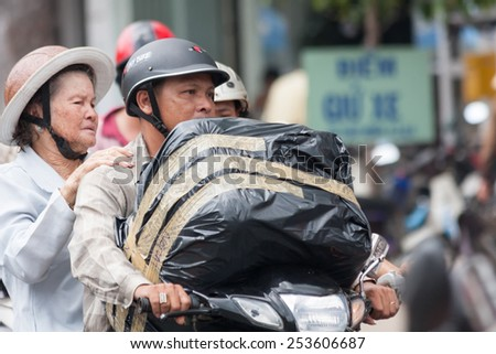 Ho Chi Minh City, Vietnam-30th Oct 2013: Man and woman carrying large parcel on a motorbike. Motorbikes are used to transport all manner of items across the city. - stock photo
