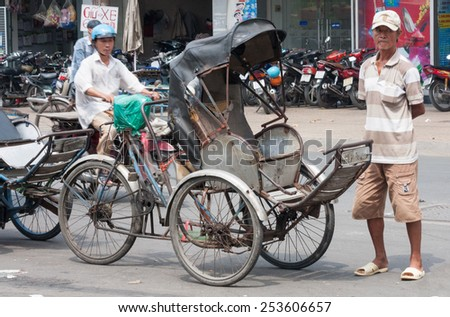 Ho Chi Minh City, Vietnam-30th Oct 2013: Rickshaw and driver waiting for a passenger. Motorcycle ownership has greatly reduced the number of rickshaws in the city. - stock photo
