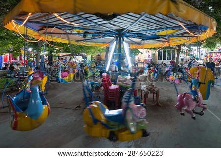 HO CHI MINH - DEC 28, 2014: An unidentified owner of a merry go round sits by it looking tired and sad. Most Vietnamese have to work really hard to earn their living in a rapidly developing country. - stock photo