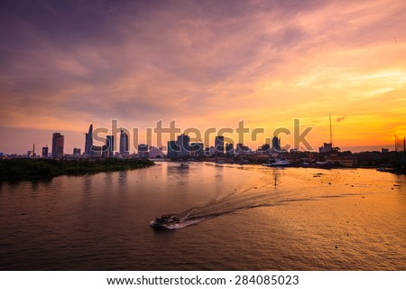 Ho Chi Minh's Panorama view over the Saigon River. Dramatic lighting spectacular sunset is highlighted by a canoe surfing on the water at a faster rate - stock photo