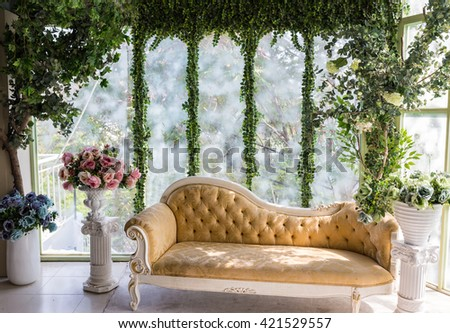 Ho Chi Minh, Vietnam - April 16, 2015: Interior design for a living room with long chair to relax and flower around. LCL Glass is used to get the sun light. - stock photo