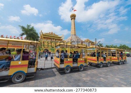 HO CHI MINH, VIETNAM - APRIL 28, 2015: Unidentified people go by a train in Dainam amusement park, 40 km away from the city. The park is so large (450 hectares) that one cannot just walk around. - stock photo