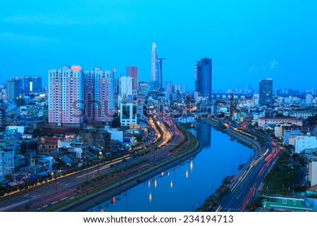 HO CHI MINH, VIETNAM - AUGUST 31, 2013 : Arial view at  Vo Van Kiet Highway in Ho Chi Minh city with the bridge cross the canal, buildings and traffic light trail at blue hour - stock photo