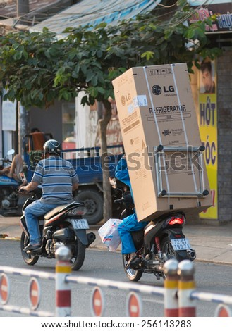 HO CHI MINH, VIETNAM - FEB 17, 2015: An unidentified man drives a new refrigerator on his motorcycle back seat. For foreigner surprise locals manage to take any load on their tiny motorcycles. - stock photo