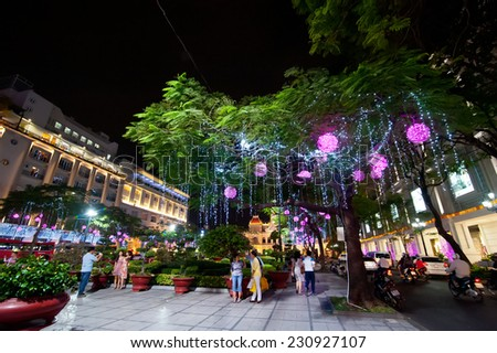HO CHI MINH, VIETNAM - JAN 21, 2014: Scene of night life at Ho Chi Minh City (Saigon). Local people and tourists enjoying New Year decoration in most attractive tourists city in Vietnam - stock photo