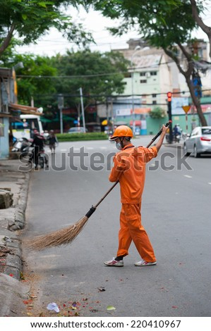 HO CHI MINH, VIETNAM - JULY 6, 2014: An unidentified street sweeper in an orange uniform sweeps a road in the downtown. - stock photo