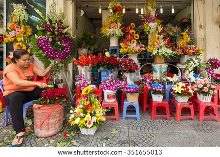 HO CHI MINH VILLE, VIETNAM, FEBRUARY 24, 2015 : Woman preparing flower composition for selling during the Chinese new year, called Tet, at the Ben Thanh market in Ho Chi MInh (Saigon), Vietnam - stock photo