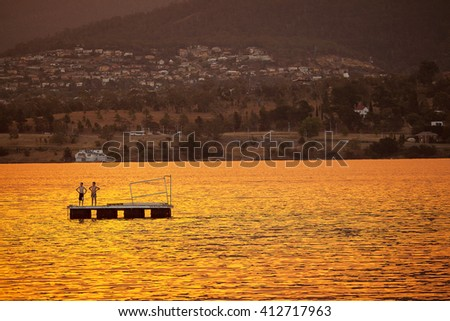 Hobart, Tasmania-January 4, 2013. Two small boys playing at sunset on a pontoon moored on the River Derwent, Hobart, Tasmania - stock photo