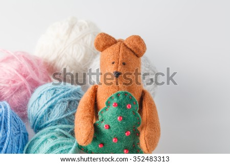 Hobby needlework concept. Handmade felt toy bear with colored wool clew - stock photo