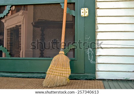 hobo cat sign on green door with old broom - stock photo