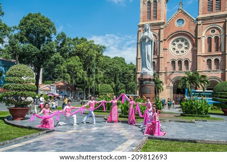 HOCHIMINH CITY, VIETNAM - AUGUST 7: the dancers performing in front of Notre Dame cathedral in Ho Chi Minh City, Vietnam on August 7, 2014. Hochiminh city is the biggest city in Vietnam. - stock photo