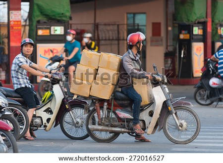HOCHIMINH, VIETNAM - APRIL 19, 2015: An unidentified motorcyclist drives several boxes in Truong Chinh Street during rush hours. The main means of cargo transportation in Vietnam is motorcycle. - stock photo