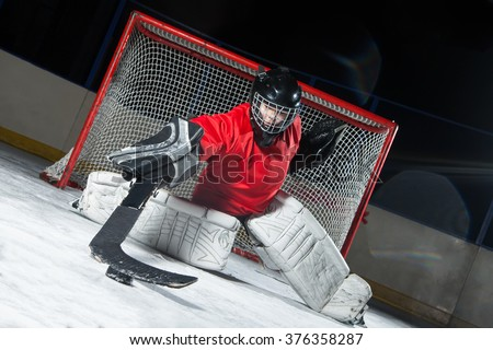 Hockey goalie blocking a puck with stick - stock photo