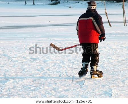 Hockey on a frozen lake. Kid playing hockey. Winter idyllic theme - stock photo