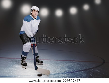 Hockey player on the ice in arena lights - stock photo