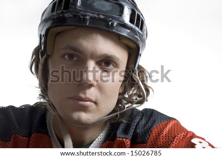 Hockey player wearing a hockey helmet stares with a serious expression. Horizontally framed photograph - stock photo