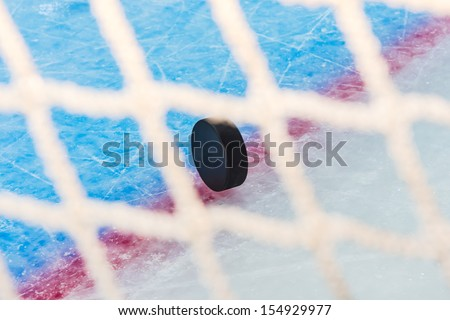 Hockey puck stand on side on goal line. View through goal net - stock photo