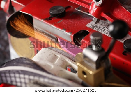 Hockey skate getting sharpened on a machine  - stock photo
