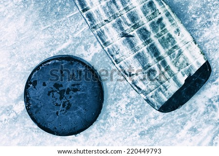 Hockey Stick and Puck. Surface of Outdoor Ice Rink Replete with Skate Marks. Ice Background.  - stock photo