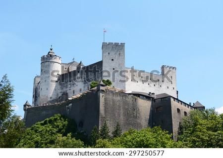 Hohensalzburg Fortress in Salzburg, Austria, with the Austrian flag flying against a blue summer sky - stock photo
