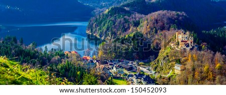 Hohenschwangau Castle with village on left, near the Neuschwanstein Castle, Germany. View from south-east, Castle on the right, Alpsee on the left.  - stock photo