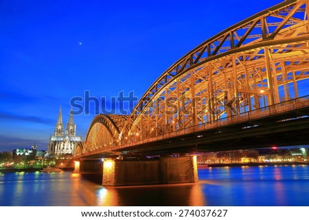 Hohenzollern bridge across Rhine river and distant Gothic Cathedral at sunset, Cologne, Germany - stock photo