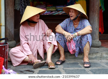 HOI AN, VIETNAM - AUG 19,2013: Unidentified old ladies chit chat  on the street in Hoi An city, Da Nang province, Vietnam. Hoi An is recognized as a World Heritage Site by UNESCO.  - stock photo