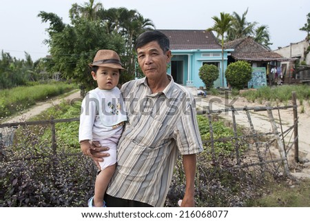 HOI AN - VIETNAM - JANUARY 9, 2014 Proud father and son in front of their house in Hoi An, Vietnam. The young boy is wearing the hat of his father.  - stock photo