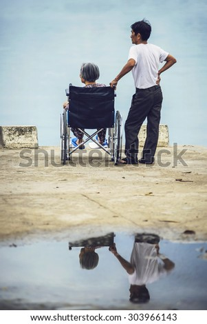 HOI AN, VIETNAM, JUNE 15: careful son with his disabled senior elderly mother at wheelchair in watching the river, on June 15, 2015, in Hoi An, Vietnam - stock photo