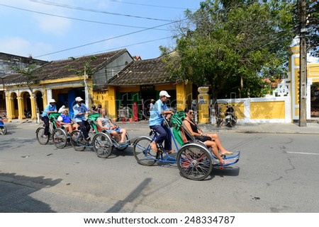 HOIAN, VIETNAM, JANUARY 23: Cyclo caring tourists in ancient Hoian town on January 23, 2015 in Hoian, Vietnam. Hoian is recognized as a World Heritage Site by UNESCO. - stock photo