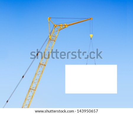 hoisting crane with empty board against the blue sky - stock photo