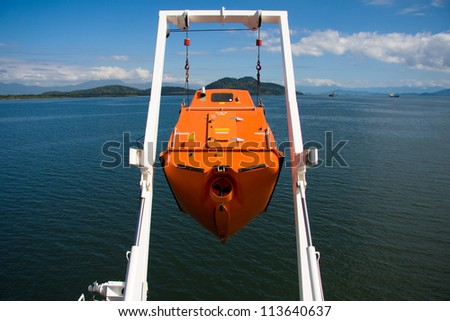 Hoisting ship's free fall life boat after training drill. - stock photo