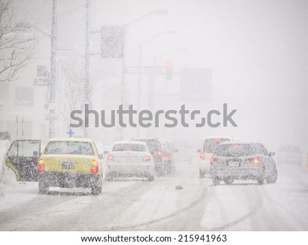 HOKKAIDO, JAPAN - DEC 15: Blizzard on the Road of Sapporo city made bad Visibility for drivers during winter snowstorm on Dec 15, 2011 in Sapporo, Hokkaido, Japan. - stock photo