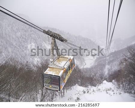 HOKKAIDO, JAPAN - DEC 16: Kurodake ropeway car ascending to the 5th Station halfway up to the summit of Mount Kurodake that towers over Sounkyo Onsen on Dec 16, 2011 in Central Hokkaido, Japan.. - stock photo