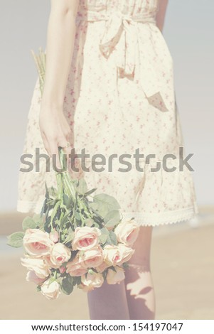 Holding A Bunch Of Flowers A Retro Woman Walks Along The Beach In Sadness After A Bitter Breakup - stock photo