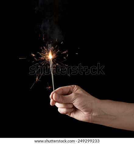 Holding a burning sparkler, low-key composition isolated over the black background - stock photo