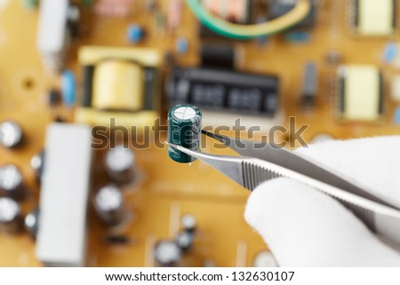 holding a capacitor with tweezers in front of a circuit board - stock photo