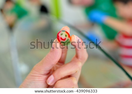 Holding a caramel candy with a smile print - stock photo