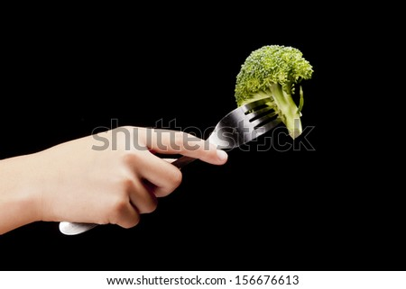 Holding a fork and broccoli. - stock photo