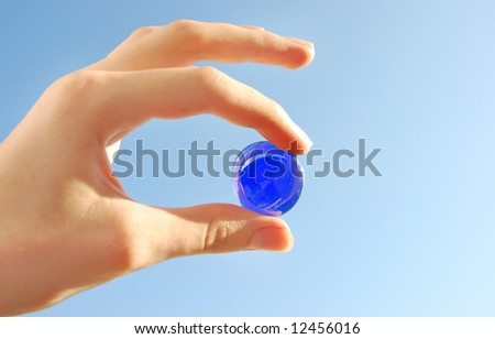 holding a glass marble - stock photo