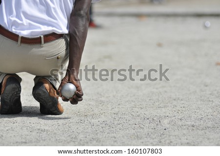 holding a petanque ball to make a throw - stock photo